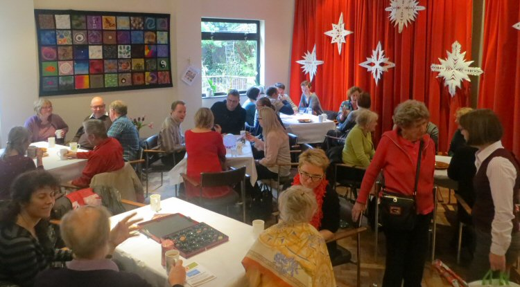 The church hall, full of people sitting round tables drinking cups of tea and coffee, engaging in conversation.