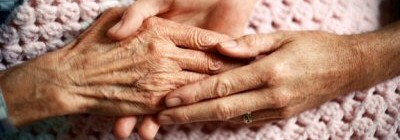 The hands of a very old person, resting on a crochet blanket, and gently held by the hands of another person.