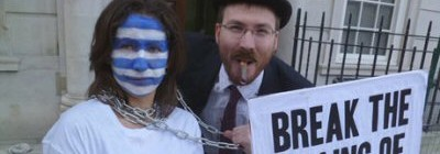 Two protestors, one in a bowler hat and smoking a cigar, another with the flag of Greece painted on their face and with chains wrapped around their neck. They hold a banner which reads 'break the chains of debt'.