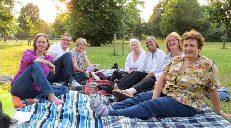 A group of seven people sitting on picnic blankets in the park on a summer's evening for an outdoor 'Heart and Soul' spiritual gathering.