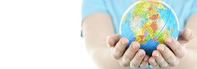 A person with outstretched arms holding a small globe of the world in their hands.