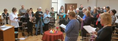 The congregation of Kensington Unitarians are pictured standing in a service and singing from hymnbooks.