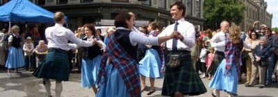 A group of people in traditional Scottish dress, including kilts and sashes, doing country dancing in the street.