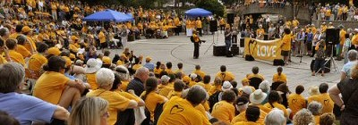 A large gathering of Unitarian Universalists wearing yellow 'Standing on the Side of Love' T-shirts at a demonstration.